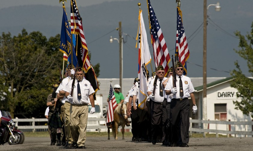 Color Guard units from American Legion Post 199 of Woodstock, left, and Post 2447 of Edinburg,  parade toward the  grandstand at the Shenandoah County Fairgrounds during the start of the Veterans Tribute on Thursday. Rich Cooley/Daily